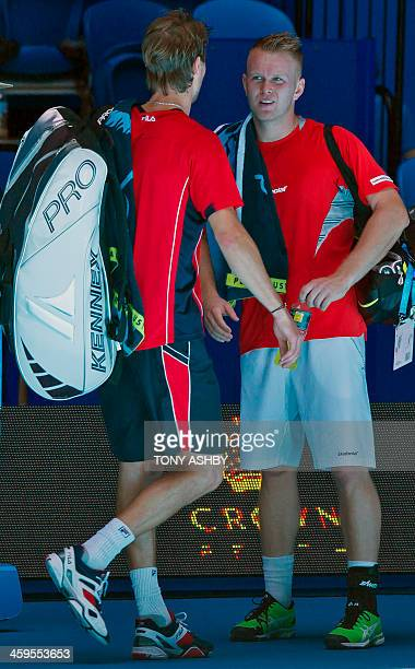 Andreas Seppi of Italy retires ill and chats with Grzegorz Panfil of Poland during their first session men's singles match on day one of the Hopman...
