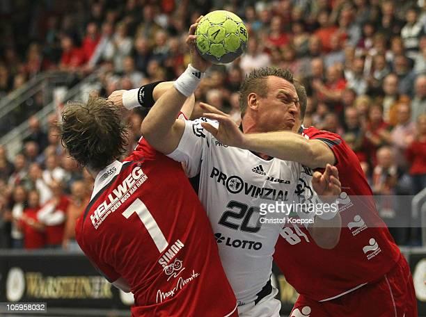 Andreas Simon of AhlenHamm and Thomas Lammers of AhlenHamm tackle Christian Zeitz of Kiel during the Toyota Handball Bundesliga match between HSG...