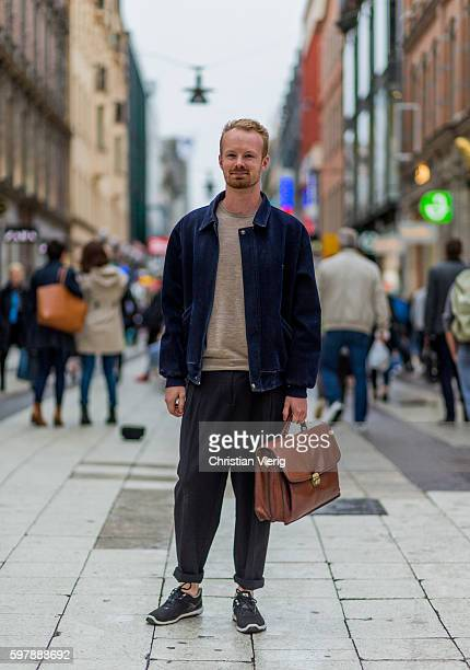 Andreas Uneby wearing a blue denim jacket dark jogger pants beige sweater and leather hand bag outside By Malina during the first day of the...
