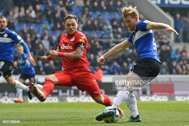 Andreas Voglsammer of Bielefeld kicks the ball past Rafael Czichos of Kiel during the Second Bundesliga match between DSC Arminia Bielefeld and...