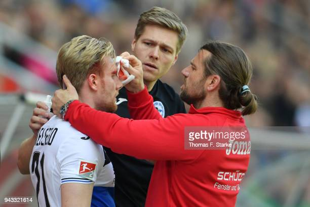 Andreas Voglsammer of Bielefeld receives medical treatment by physiotherapist Michael Schweika and soctor Stefan Budde during the Second Bundesliga...