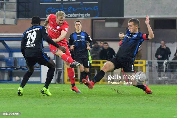 Andreas Voglsammer of Bielefeld scores against Jamilu Collins and Uwe Huenemeier of Paderborn during the Second Bundesliga match between SC Paderborn...