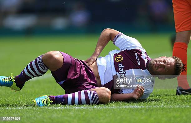 Andreas Weimann of Aston Villa holds his hip as he lies injured before being substituted