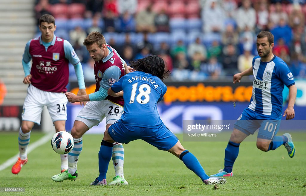Andreas Weimann of Aston Villa is challenged by Roger Espinoza of Wigan Athletic during the Barclays Premier League match between Wigan Athletic and Aston Villa at DW Stadium on May 19, 2013 in Wigan, England.