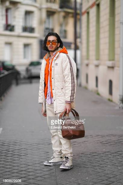 Andree Dubois wears aviator sunglasses, a white puffer coat from Adidas, an orange winter puffer jacket, a purple and white striped shirt from...