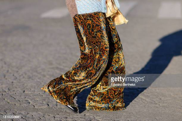 Andree Dubois wears silk multicolor flare pants with damask print from Y Project, shoes from Y Project, holds a bouquet of flowers, on March 06, 2021...