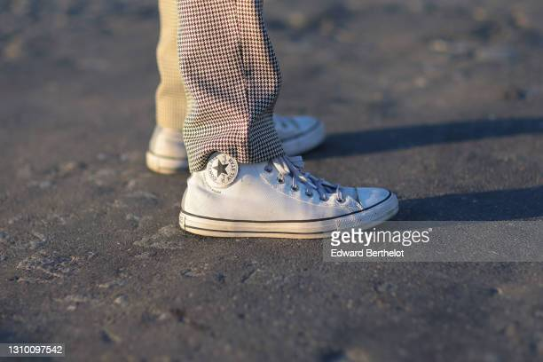 Andree Dubois wears suit pants with black and white houndstooth printed patterns from Glenn martens x Peace Bird, white sneakers shoes from Converse,...