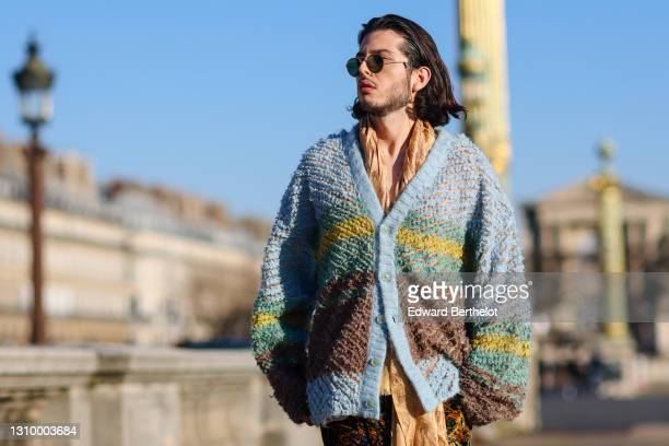 Andree Dubois wears sunglasses, a blue green and brown striped wool oversized cardigan from Y-Project, a beige and brown scarf with printed...