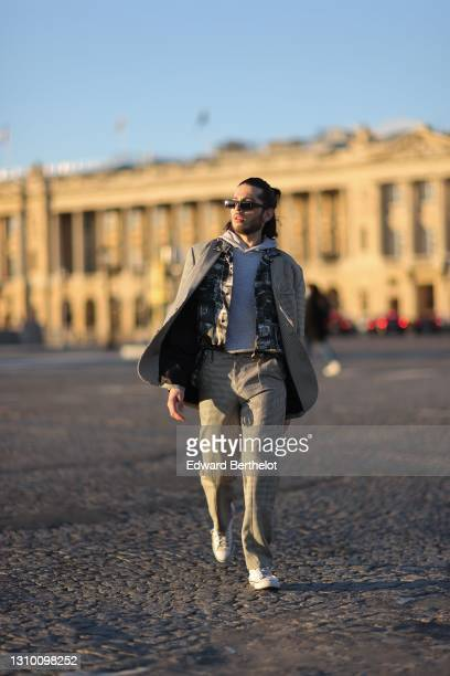 Andree Dubois wears sunglasses, a gray hoodie sweater from HM, a black and white printed shirt from Y Project, an oversized blazer jacket with black...