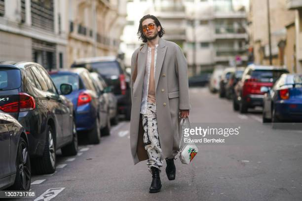 Andree Dubois wears sunglasses, a gray long coat from Dior, a white shirt, a beige top from Margiela, a white leather bag with printed palm trees...