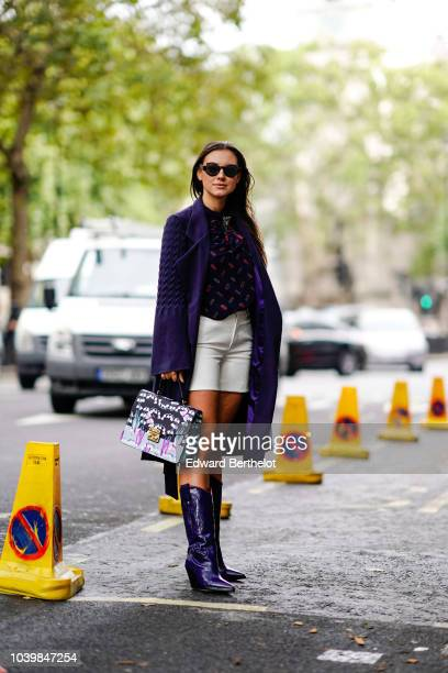 Andreea Cristea wears a blue coat a blue mesh shirt with colored features a green skirt blue pvc boots a bag during London Fashion Week September...