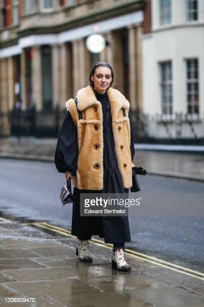 Andreea Cristea wears a brown winter fluffy faux fur oversized coat, a large black dress with puff sleeves, a black leather crocodile pattern bag,...