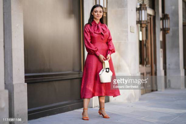 Andreea Cristea wears a red dress with printed stars, a white bag, orange shoes with silver metallic heels shaped as spheres, during London Fashion...