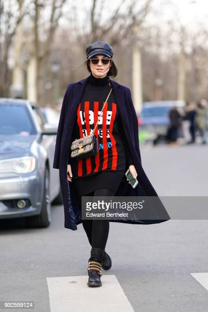 Andreea Cristea wears sunglasses a black cap a navy blue coat a black turtleneck with red stripes and white figures patterned on the front a black...