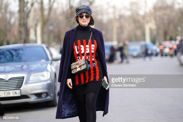 Andreea Cristea wears sunglasses a black leather cap a navy blue coat a black turtleneck with red stripes and white figures patterned on the front a...