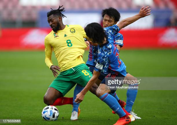 Andre-Frank Zambo Anguissa of Cameroon holds off Gaku Shibasaki and Takumi Minamino of Japan during the international friendly match between Japan...