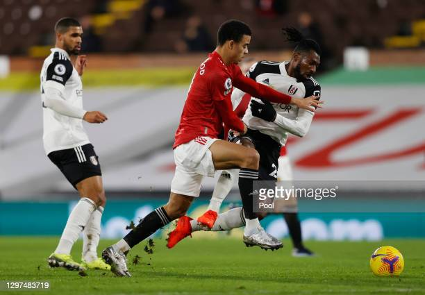 Andre-Frank Zambo Anguissa of Fulham and Mason Greenwood of Manchester United battle for possession during the Premier League match between Fulham...