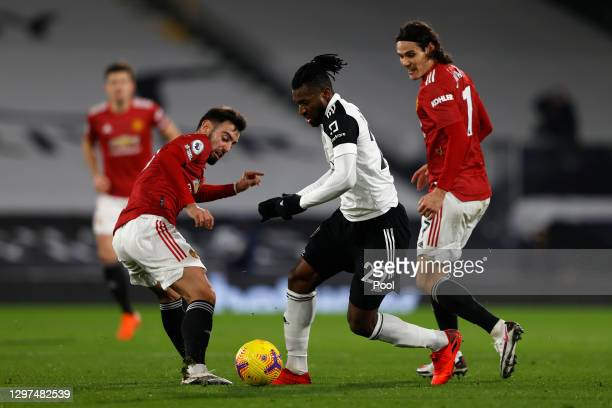 Andre-Frank Zambo Anguissa of Fulham battles for possession with Bruno Fernandes of Manchester United during the Premier League match between Fulham...
