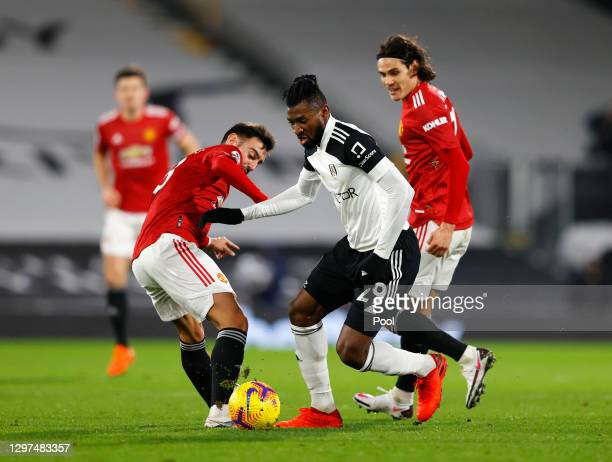 Andre-Frank Zambo Anguissa of Fulham is challenged by Bruno Fernandes of Manchester United during the Premier League match between Fulham and...