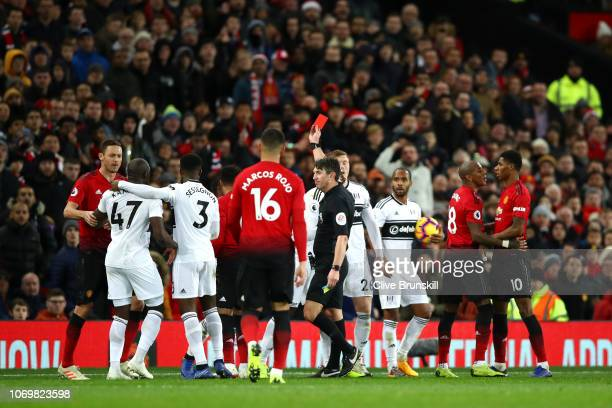 AndreFrank Zambo Anguissa of Fulham is shown a red card by referee Lee Probert during the Premier League match between Manchester United and Fulham...