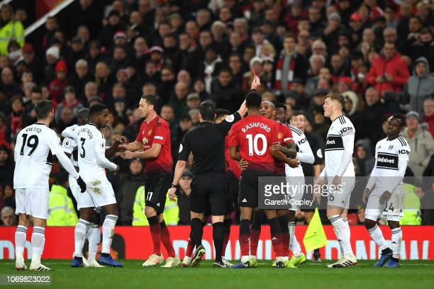 AndreFrank Zambo Anguissa of Fulham is shown a yellow card by referee Lee Probert during the Premier League match between Manchester United and...
