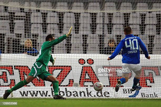 Andrei Cristea of Karlsruhe scores his team's first goal against goalkeeper David Yelldell of Duisburg during the Second Bundesliga match between...