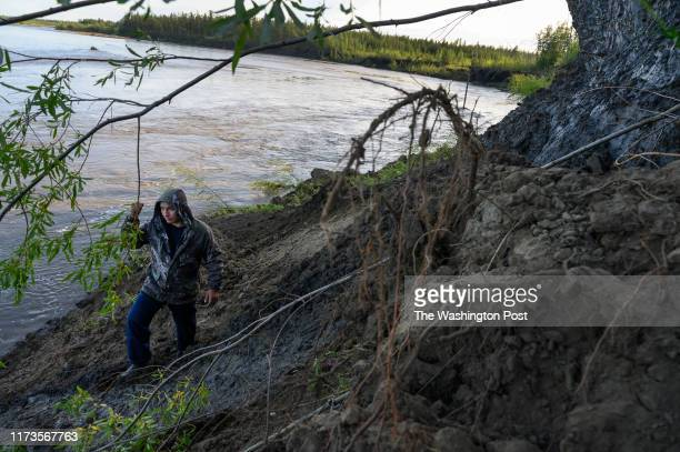 Andrei Danilov, a commercial truck driver and part time mammoth tusk hunter, walks below melting permafrost, right, in an area rich in mammoth tusks...