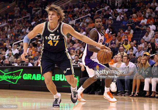 Andrei Kirilenko of the Utah Jazz drives the ball past Earl Clark of the Phoenix Suns during the preseason NBA game at US Airways Center on October...