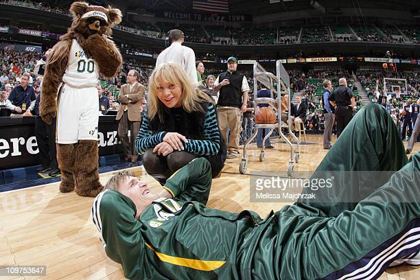 Andrei Kirilenko of the Utah Jazz stretches on the court while talking with his wife Masha Kirilenko prior to the game against the Denver Nuggets at...
