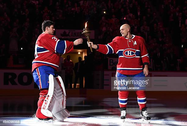 Andrei Markov hands over the flame to Carey Price of the Montreal Canadiens during the pre game ceremony prior to the NHL game against the New York...