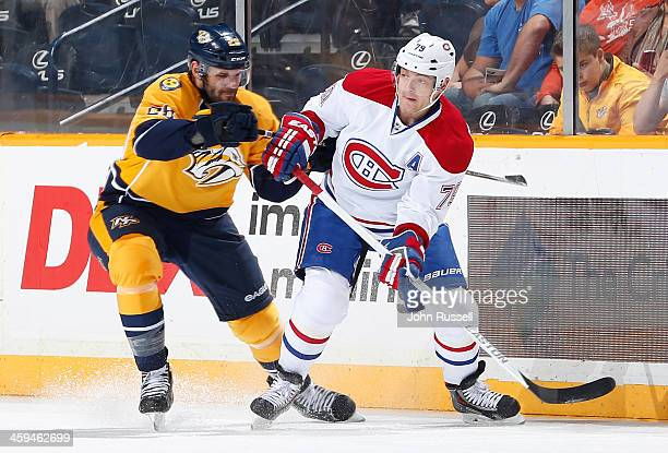 Andrei Markov of the Montreal Canadiens skates against Paul Gaustad of the Nashville Predators at Bridgestone Arena on December 21 2013 in Nashville...