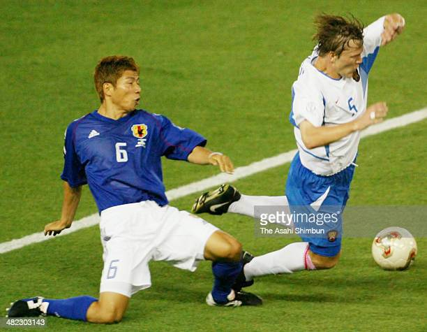 Andrei Solomatin of Russia is tackled by Toshihiro Hattori of Japan during the FIFA World Cup Korea/Japan Group H match between Japan and Russia at...