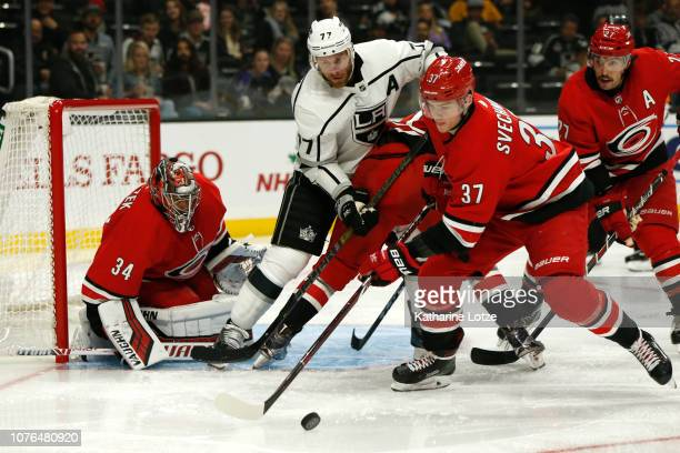 Andrei Svechnikov of the Carolina Hurricanes and Jeff Carter of the Los Angeles Kings fight for control of the puck in front of the Hurricane goal...