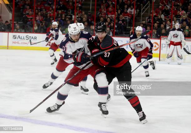Andrei Svechnikov of the Carolina Hurricanes battles for position on the ice with Josh Anderson of the Columbus Blue Jackets during an NHL game on...