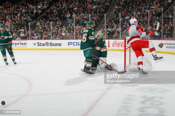 Andrei Svechnikov of the Carolina Hurricanes celebrates after scoring the game winning goal in overtime while Jared Spurgeon and Devan Dubnyk of the...