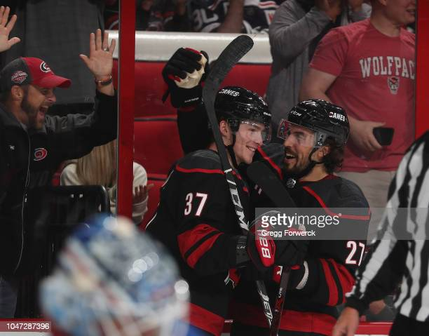 Andrei Svechnikov of the Carolina Hurricanes is congratulated by teammate Justin Faulk after scoring his first NHL goal during an NHL game against...
