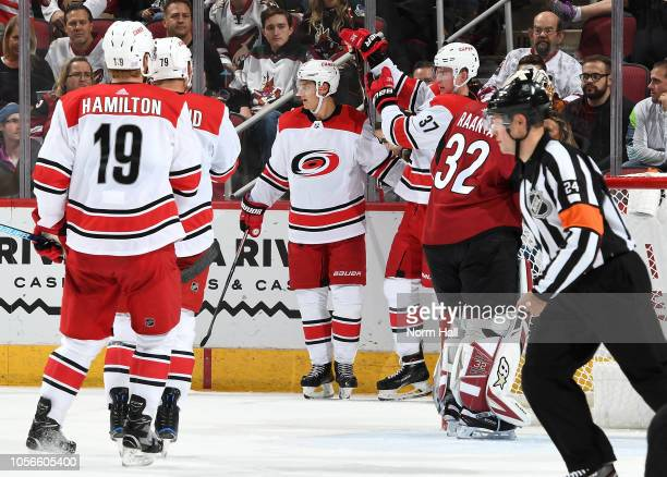 Andrei Svechnikov of the Carolina Hurricanes is congratulated by teammate Sebastian Aho after scoring a goal against the Arizona Coyotes as Dougie...