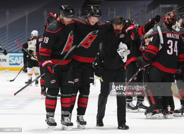 Andrei Svechnikov of the Carolina Hurricanes is helped off the ice by teammate Dougie Hamilton and a team trainer in the third period of Game Three...