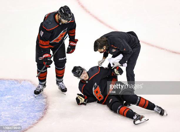 Andrei Svechnikov of the Carolina Hurricanes is tended to by the trainer after sustaining a knee injury against the Boston Bruins during the third...