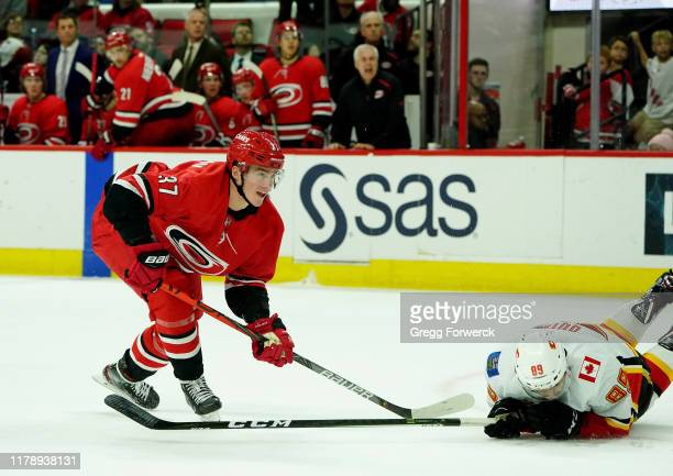 Andrei Svechnikov of the Carolina Hurricanes shoots the puck and Alan Quine of the Calgary Flames goes down on the ice to block the shot during an...