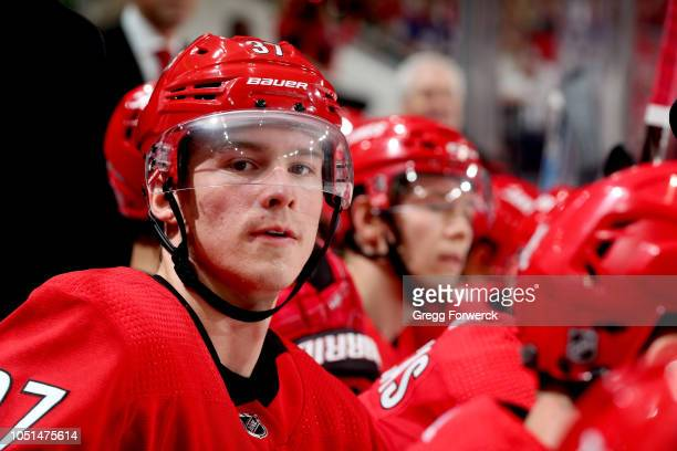 Andrei Svechnikov of the Carolina Hurricanes watches action on the ice from the bench area during an NHL game against the New York Islanders on...