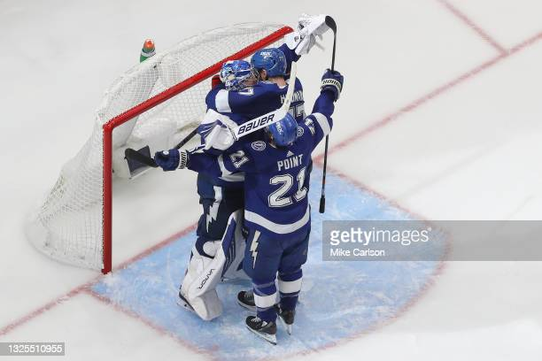 Andrei Vasilevskiy, Brayden Point and Victor Hedman of the Tampa Bay Lightning celebrate after defeating the New York Islanders 1-0 in Game Seven of...