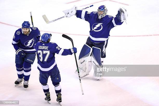 Andrei Vasilevskiy Luke Schenn and Yanni Gourde of the Tampa Bay Lightning celebrate after the gamewinning goal by Victor Hedman during the second...
