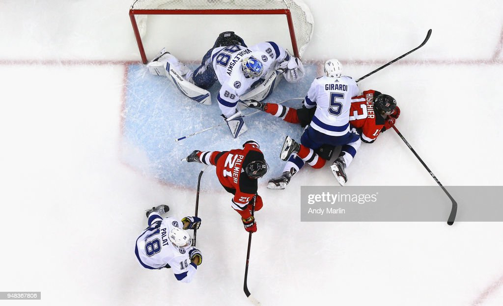 Andrei Vasilevskiy #88 of the Tampa Bay Lightning defends his net as Dan Girardi #5 checks Nico Hischier #13 of the New Jersey Devils in Game Four of the Eastern Conference First Round during the 2018 NHL Stanley Cup Playoffs at Prudential Center on April 18, 2018 in Newark, New Jersey. The Lightning defeated the Devils 3-1.