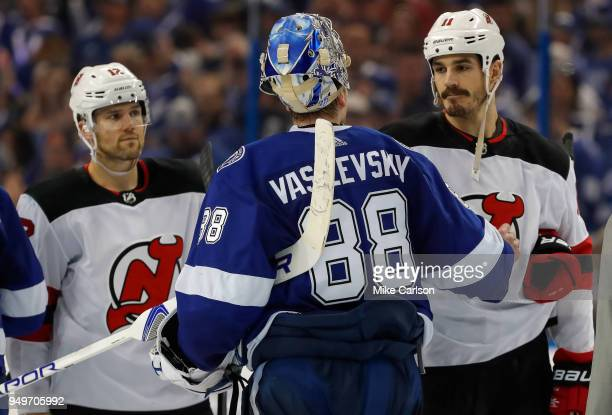 Andrei Vasilevskiy of the Tampa Bay Lightning shakes hands with Brian Boyle of the New Jersey Devils as Ben Lovejoy looks on after Game Five of the...