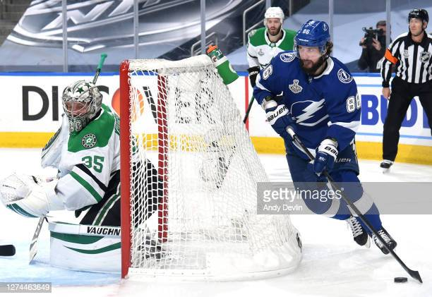 Andrei Vasilevskiy of the Tampa Bay Lightning skates with the puck behind the net of goaltender Anton Khudobin of the Dallas Stars in the second...
