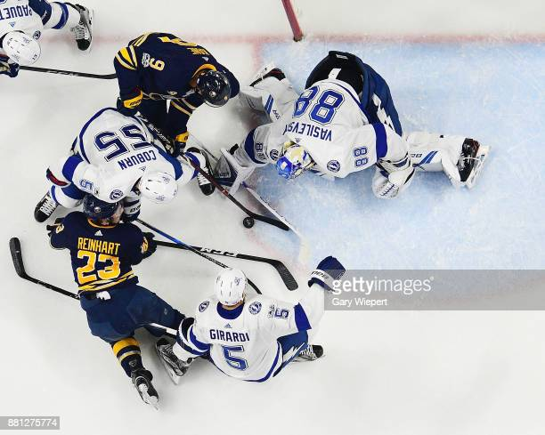 Andrei Vasilevskiy of the Tampa Bay Lightning tries to cover the puck as Evander Kane and Sam Reinhart of the Buffalo Sabres battle for it with...