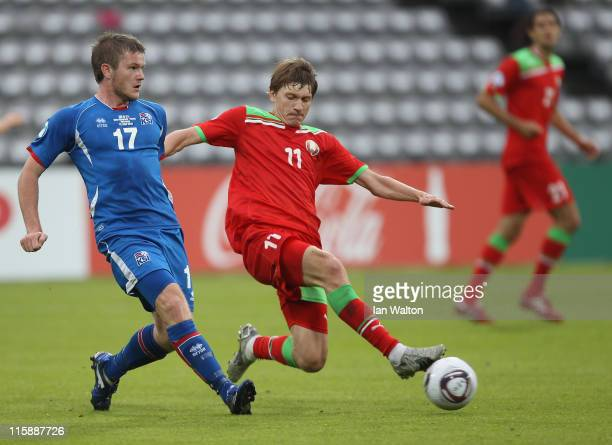 Andrei Voronkov of Belarus tries to tackle Aron Gunnarsson of Iceland during their UEFA European Under21 Championship Group A match between Belarus...