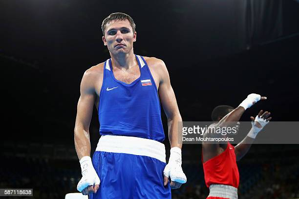 Andrei Zamkovoi of Russia looks dejected as Rayton Nduku Okwiri of Kenya celebrates victory after they compete in the Men's Welter 69kg preliminary...