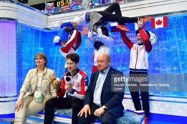 AndreiLazukin of Russia waits for his score at the kiss and cry with his team mates after competing in the Men's Single Free Skating on day two of...